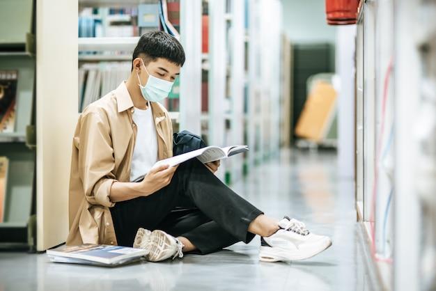 Een man met maskers zit een boek te lezen in de bibliotheek.