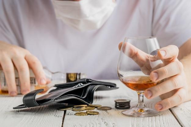 Een man met medicing masker poseren met een glas alcohol, indoor portret