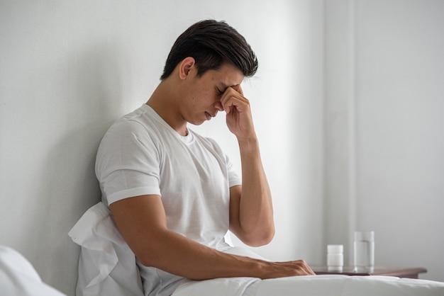 Een man met migraine houdt haar hand bij zijn neus in bed.