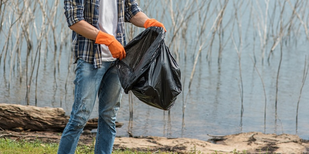 Een man met oranje handschoenen die vuilnis in een zwarte zak verzamelen.