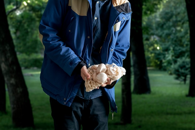 Een man met paddenstoelen in het bos. paddenstoelenseizoen verzamelen