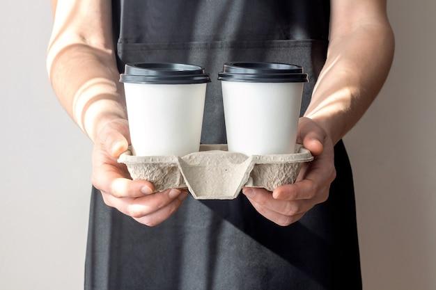 Een man met papieren wegwerpkoffiekopjes in een kartonnen dienblad