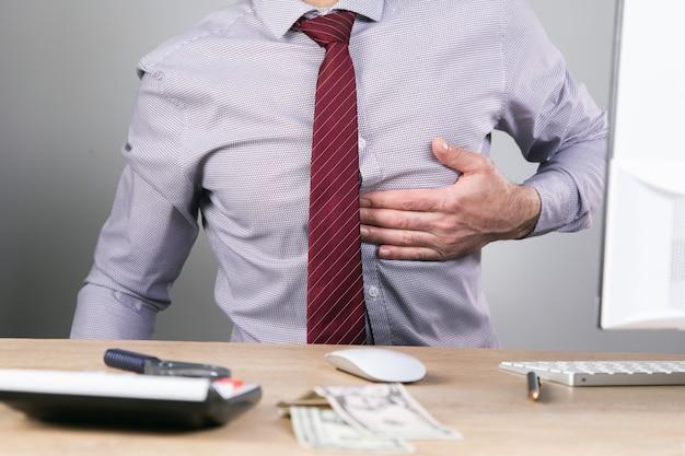 Een man met pijn in zijn hart aan zijn bureau.