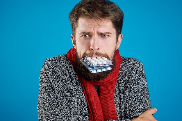 Een man met pillen in zijn tanden gebaren met zijn handen gezondheidsproblemen warme kleren rode sjaal