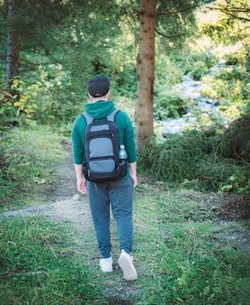 Een man met rugzak loopt in het herfstbos. alleen wandelen langs bospaden in de herfst. reisconcept.
