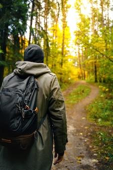 Een man met rugzak loopt in het verbazingwekkende herfstbos.