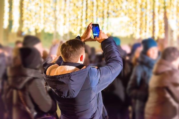 Een man met smartphone 's nachts op straat in de stad