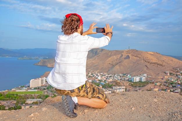 Een man met uitzicht op een panoramisch uitzicht op een prachtige kustlijn vanaf de heuvel en maakt een foto aan de telefoon