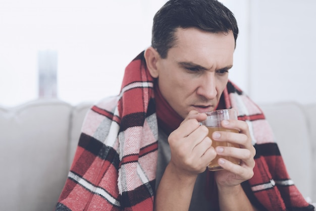 Een man met verkoudheid zit op de bank met sneez.