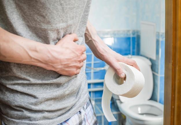 Een man met wc-papier klampt zich vast aan zijn buik. diarree.