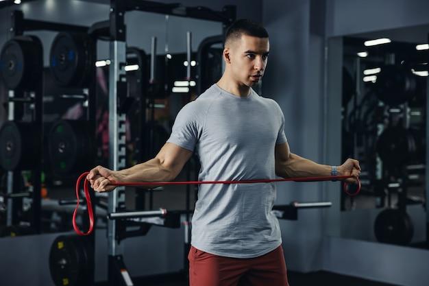 Een man met zichtbare aderen op zijn armen traint met een elastische band in een sportschool met grote spiegels en zwarte matten