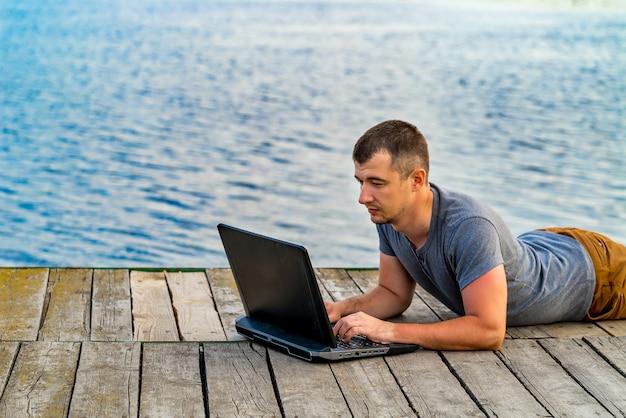 Een man met zijn notitieboekje werkt buiten aan het meer