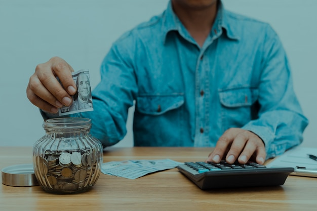 Een man met zijn spaargeld en een rekenmachine