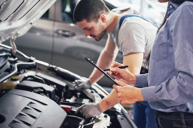Een man monteur en vrouw klant kijken naar de motorkap en bespreken reparaties