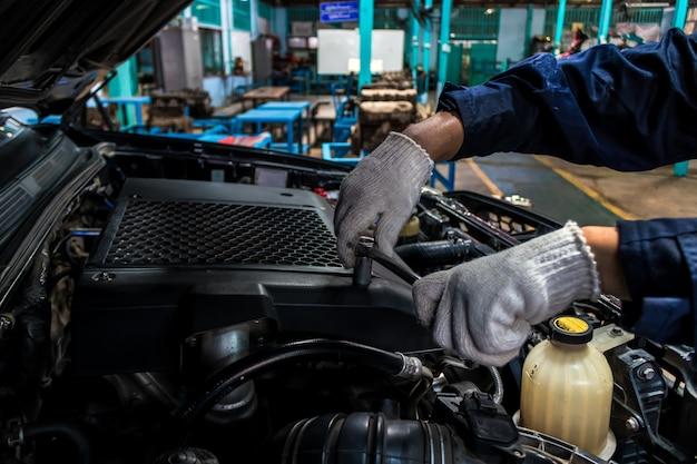 Een man-monteur repareert een auto gebruik een sleutel en een schroevendraaier om te werken