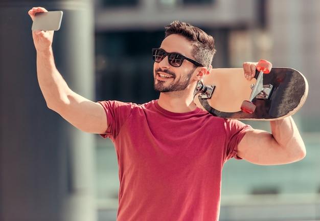 Een man neemt een selfie met een schaats in zijn handen.
