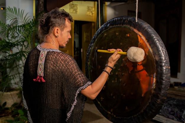 Een man oefent een klankgong