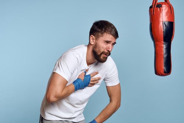 Een man oefent een stoot op een bokszak in een wit t-shirt op een blauwe ruimte.