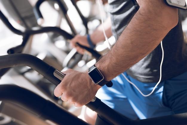 Een man oefent op een loopband in een moderne sportschool.