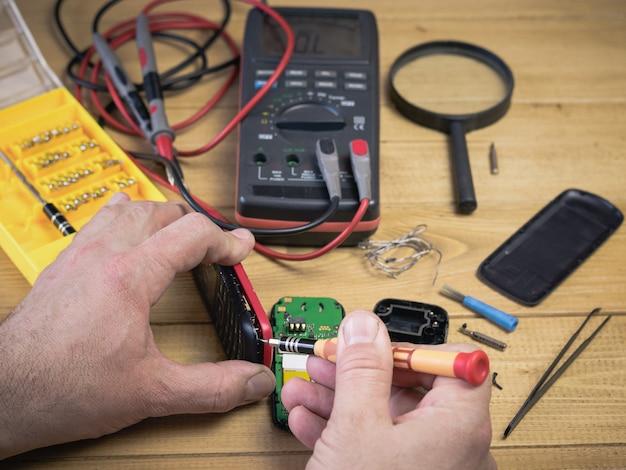 Een man onderzoekt een mobiele telefoon voor reparatie.