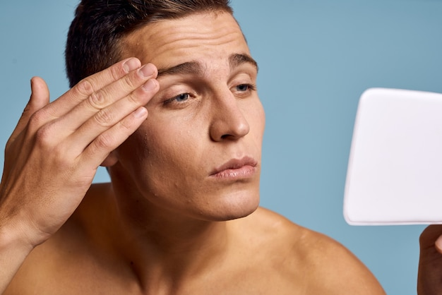 Een man onderzoekt zijn gezicht in een spiegel op een bijgesneden weergave van een blauwe achtergrond. hoge kwaliteit foto