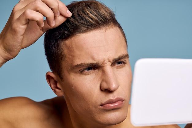 Een man onderzoekt zijn gezicht in een spiegel op een blauw