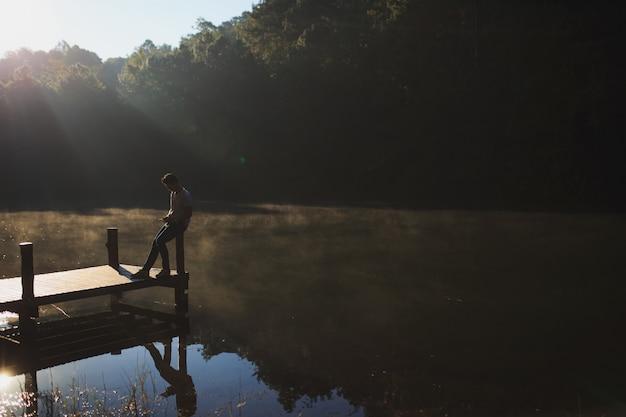 Een man ontspande op een houten brug.