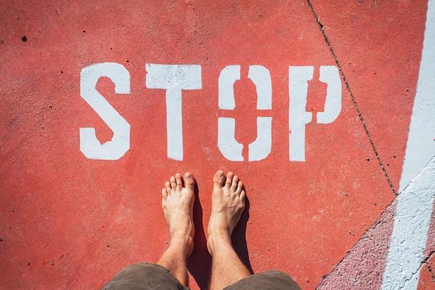 Een man op blote voeten stopt bij een stopbord dat op de grond is geschilderd