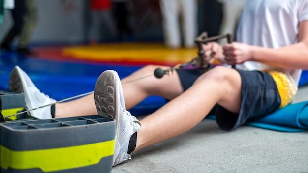 Een man op de vloer van de sportschool doet een oefening met een simulator