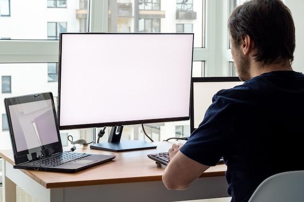 Een man op de werkplek met twee laptops en een monitor bij het raam