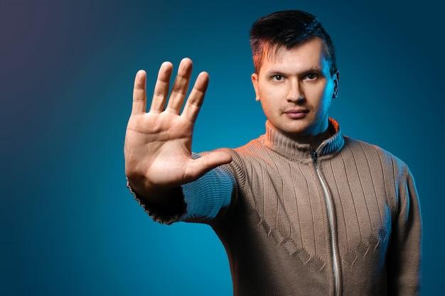 Een man op een blauwe achtergrond in een gele jas toont zijn hand om te stoppen.