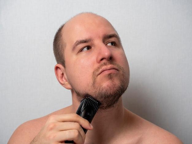 Een man op een grijze achtergrond scheert zijn baard met een elektrisch scheerapparaat. hij is in gedachten verzonken en kijkt weg terwijl hij zijn haar trimt. schoonheid en verzorging voor mannen thuis.