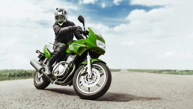 Een man op een groene motorfiets draait zich om voor de camera