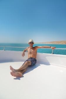 Een man op een jacht dat de zee vaart.