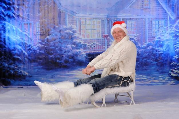 Een man op een slee. kerstfotosessie in de studio.