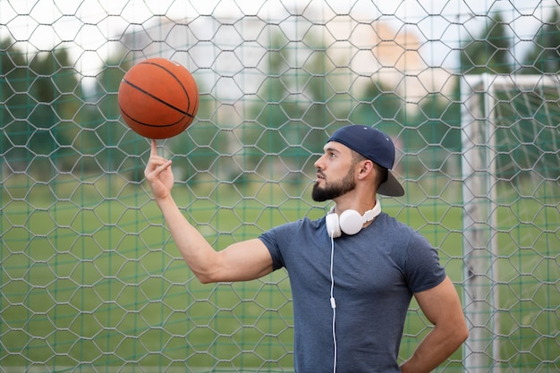 Een man op een straat speeltuin draait een basketbal om zijn vinger