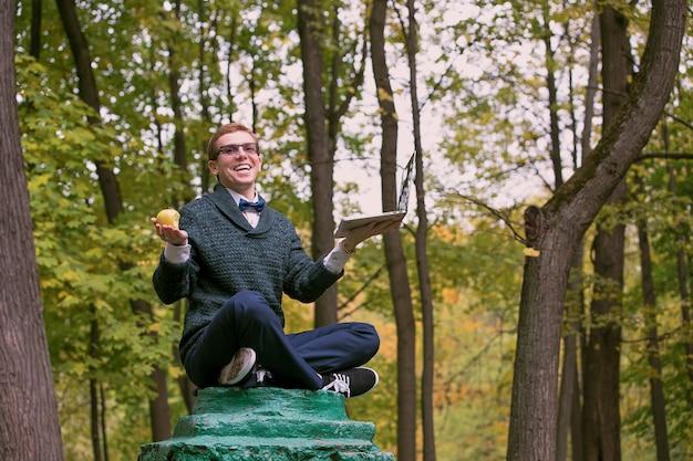 Een man op een voetstuk die zich voordoet als een standbeeld in de houding van een filosoof met appel en laptop in het herfstpark