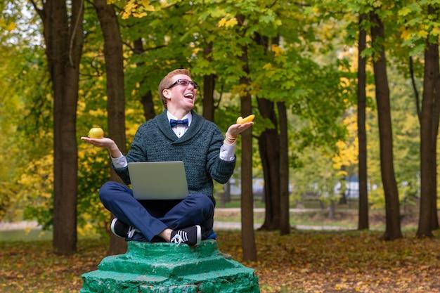 Een man op een voetstuk die zich voordoet als een standbeeld in de houding van een filosoof voordat hij een appel of een banaan kiest in het herfstpark