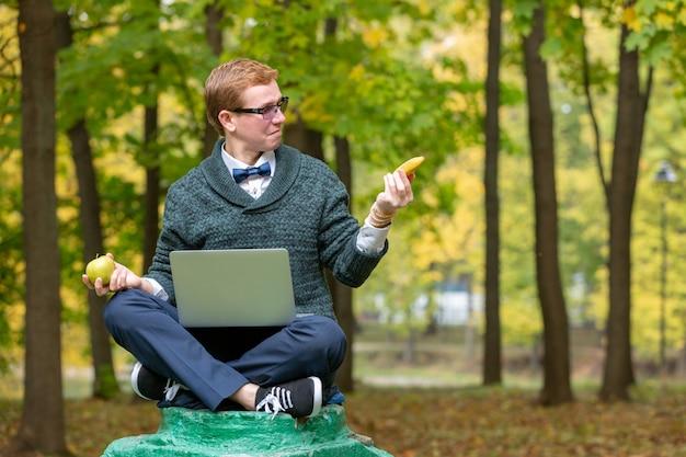 Een man op een voetstuk die zich voordoet als een standbeeld in de houding van een filosoof voordat hij in het park een appel of een banaan kiest