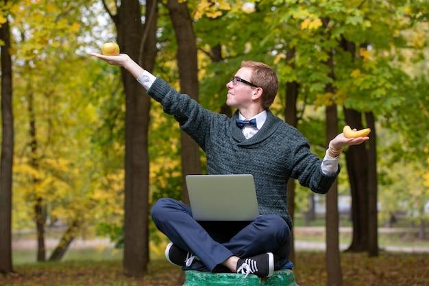 Een man op een voetstuk die zich voordoet als een standbeeld in de houding van een filosoof voordat hij in het park een appel of een banaan kiest.