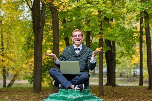 Een man op een voetstuk die zich voordoet als een standbeeld in de pose van een filosoof voordat hij een appel of een banaan kiest in het herfstpark