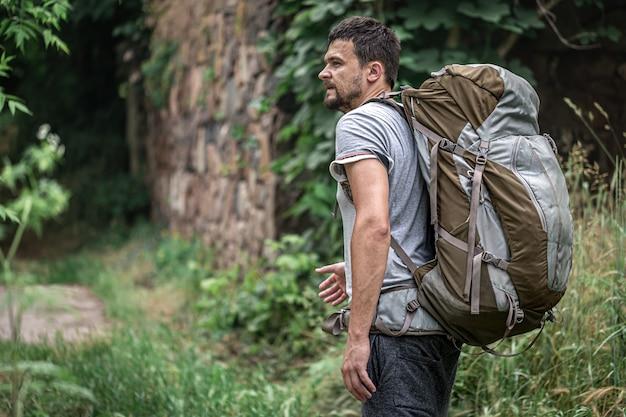 Een man op een wandeling met een grote rugzak reist in het bos.