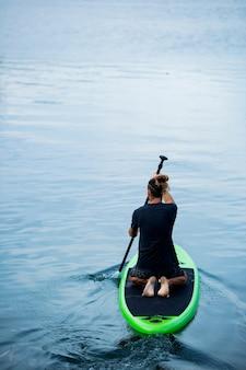 Een man op het meer rijdt op een sup board.