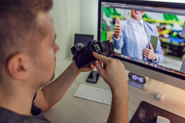 Een man op het werk houdt een camera in zijn handen terwijl hij naar een digitaal computerscherm kijkt met een foto die hij heeft gemaakt