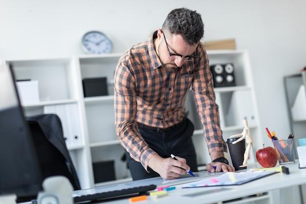 Een man op kantoor staat bij de tafel en trekt een marker op het magneetbord.