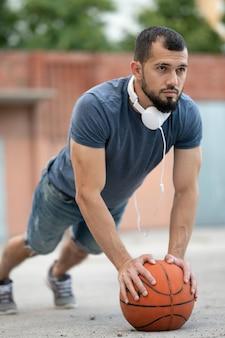 Een man op straat doet push-ups, leunend op een basketbal
