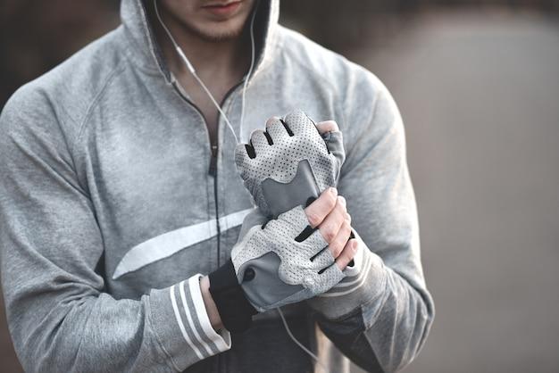 Een man op straat trekt zijn sporthandschoenen aan en bereidt zich voor op coaching.