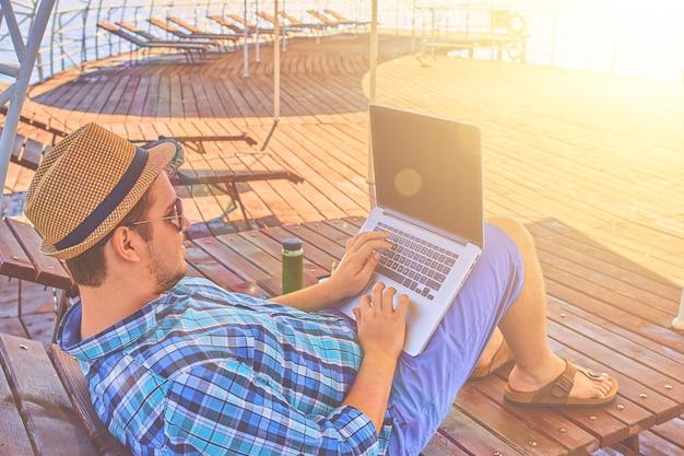 Een man op vakantie, zit op de pier en werkt.