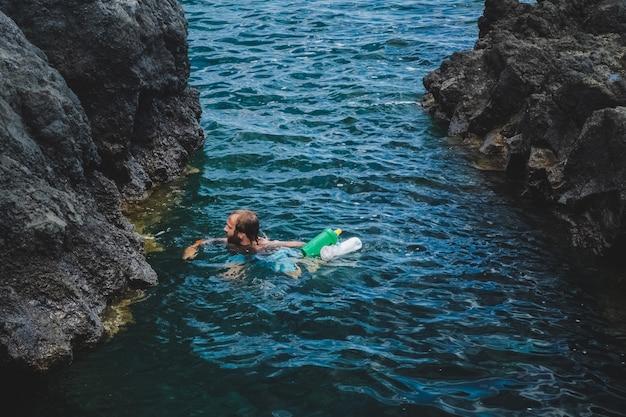 Een man op zee verzamelt plastic afval dat in het water ligt