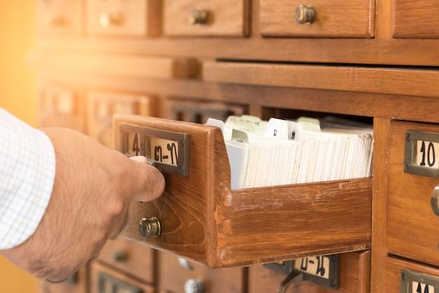 Een man opent de houten bibliotheek met opgeslagen bibliotheekindex.
